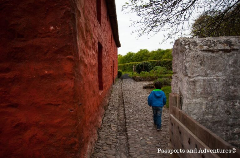 A little boy in a blue and green jacket walking along a path that runs beside a red building at St Fagans in Cardiff