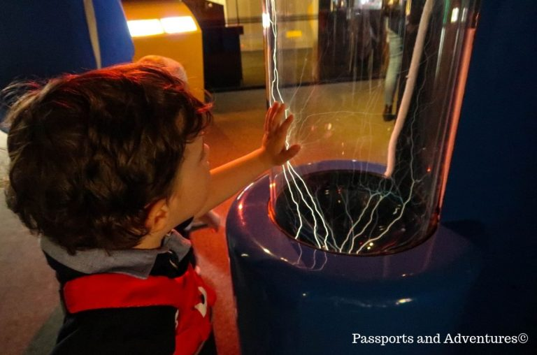 A young boy with his hand on a plastic housing to an electricity display in Techniquest, Cardiff