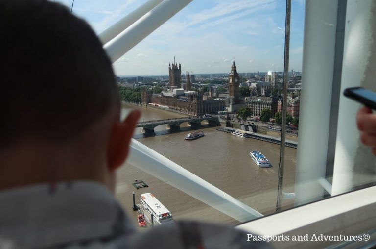 A picture of a little boy looking out the window of one of the capsules in the London Eye towards Big Ben and the Houses of Parliament