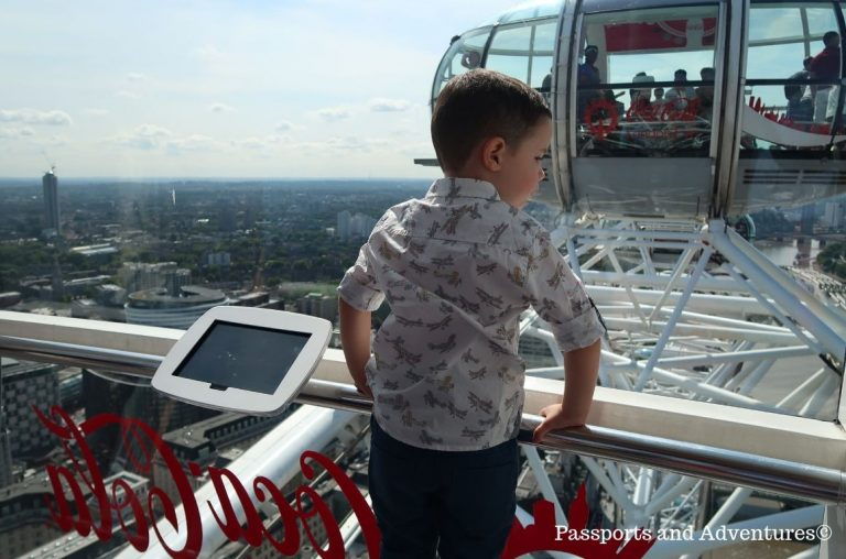 A little boy looking out of the glass windows of a capsule at the London Eye