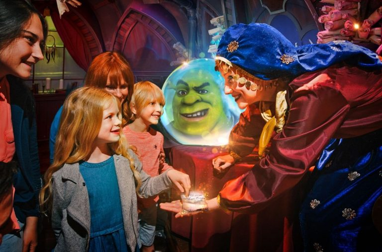 Shrek's head in a crystal ball with kids in the forefront and Esmerelda the fortune teller at Shrek's Adventure in London