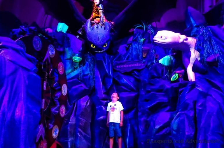 A young boy looking up at Hiccup and Toothless in the Dreamworks Shrek's Adventure attraction in London