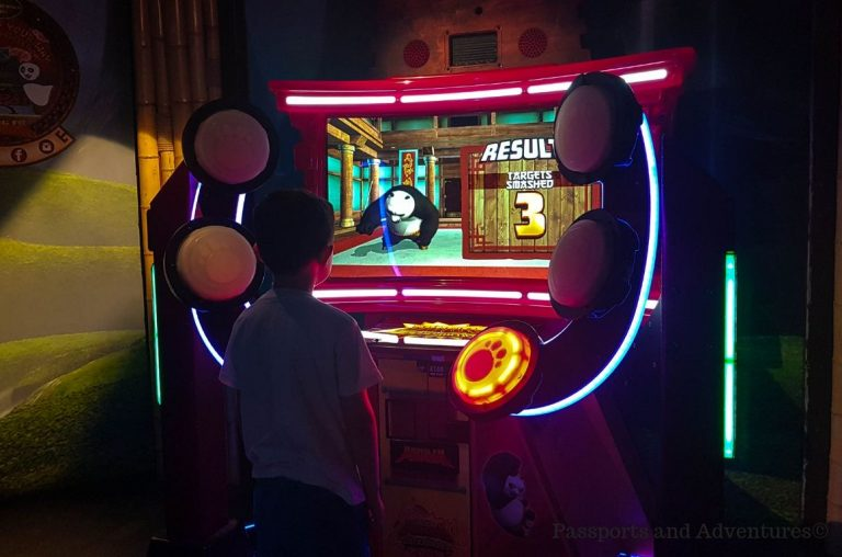 A young boy standing in front of a Kung Fo Panda arcade game at Shrek's Adventure