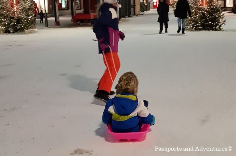 A young boy in a snowsuit being pulled around on a sled in Lapland