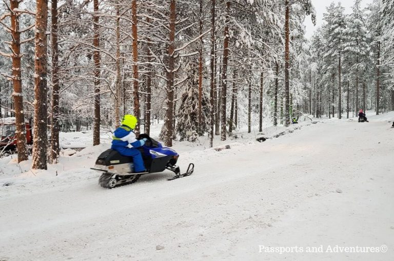 A little boy in a blue and white snowsuit on a snowmobile in Lapland