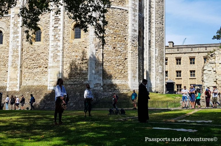Three actors on the grass in front of the White Tower at the Tower of London acting out an event