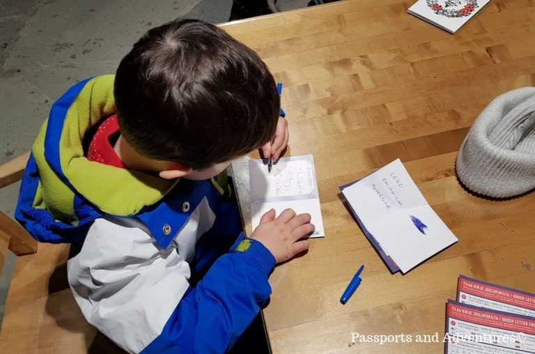 A young boy in a blue, green and white snowsuit sitting at a table writing postcards in Lapland