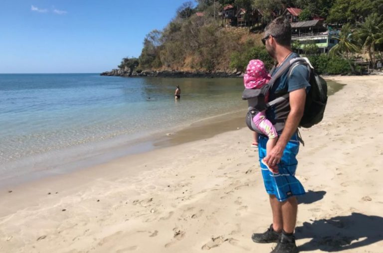 A picture of a dad with a baby in a baby carrier on a beach in Thailand