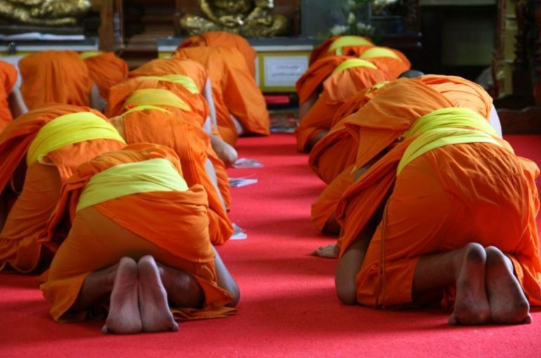 Buddhist momks on orange robes with yellow sashes praying on their knees in Thailand