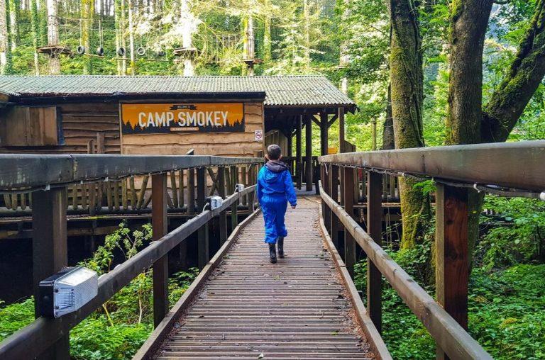 A boy in a blue rainsuit walking towards Camp Smokey at Bluestone in Wales
