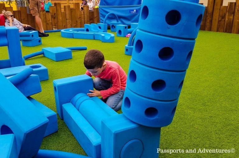 A young boy in a pink top and jeans playing with large blue soft blocks in the Imagination Garden in the Serendome at Bluestone, Wales
