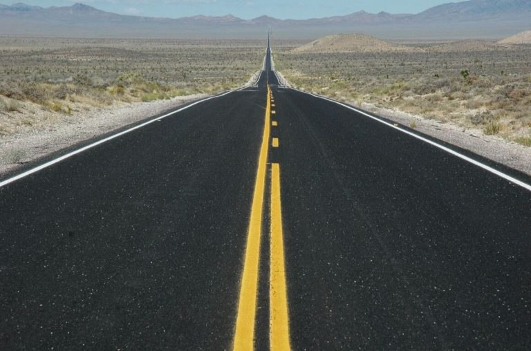 A picture of a long road of black tarmac stretching into the horizon