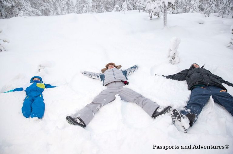 A family of three making snow angels in the snow in Finnish Lapland