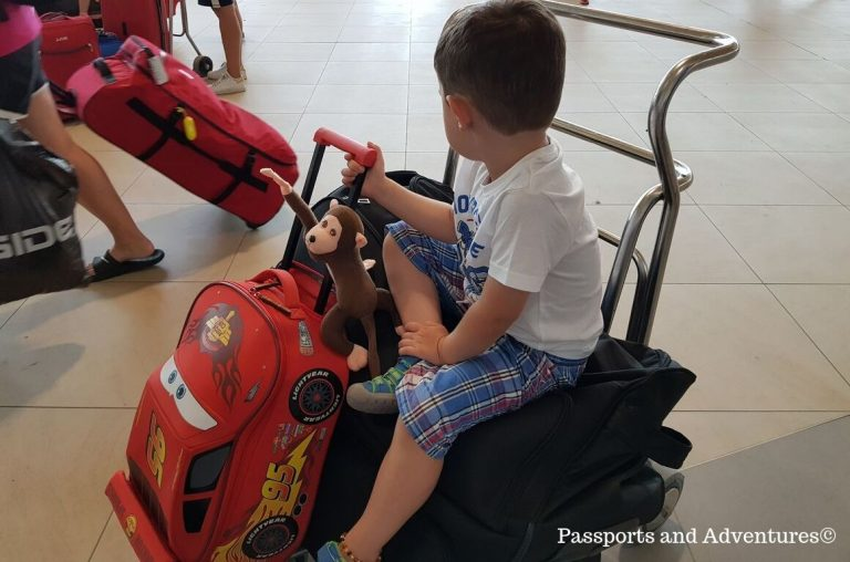 A little boy sitting on luggage on a luggage trolley in an airport