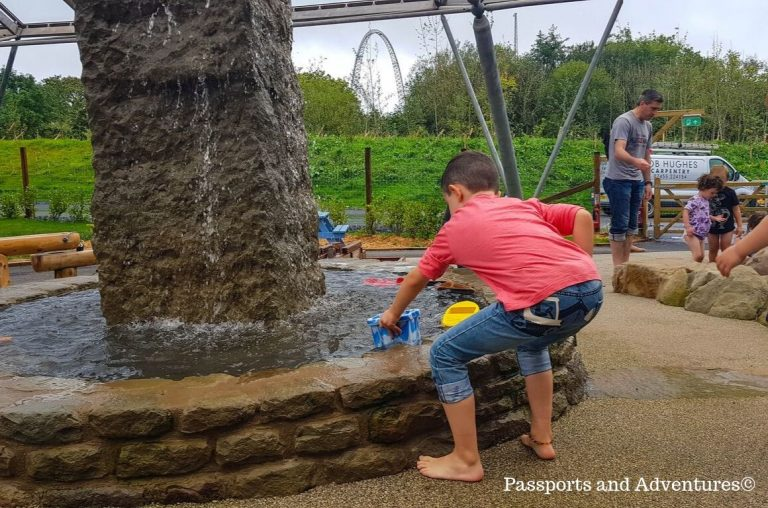 Little boy in a pink top and jeans, playing in a water area at Bluestone, Wales