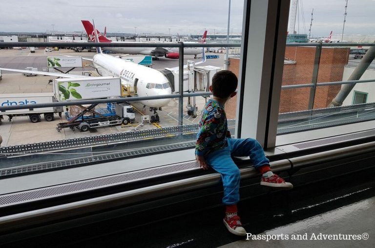 A little boy sitting at a window looking down at a Delta Airways plane in Heathrow airport