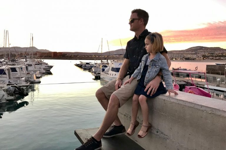 A picture of a Dad and his daughter sitting on a wall in a marina in Fuerteventura