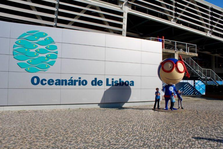 Three young kids standing with the diver outside the Oceanario de Lisboa