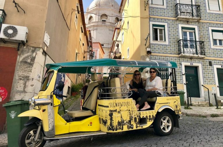 Two ladies sitting in the Tuk Tuk Lisbon Tour vehicle