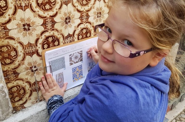 Little girl doing a tile treasure hunt in Lisbon