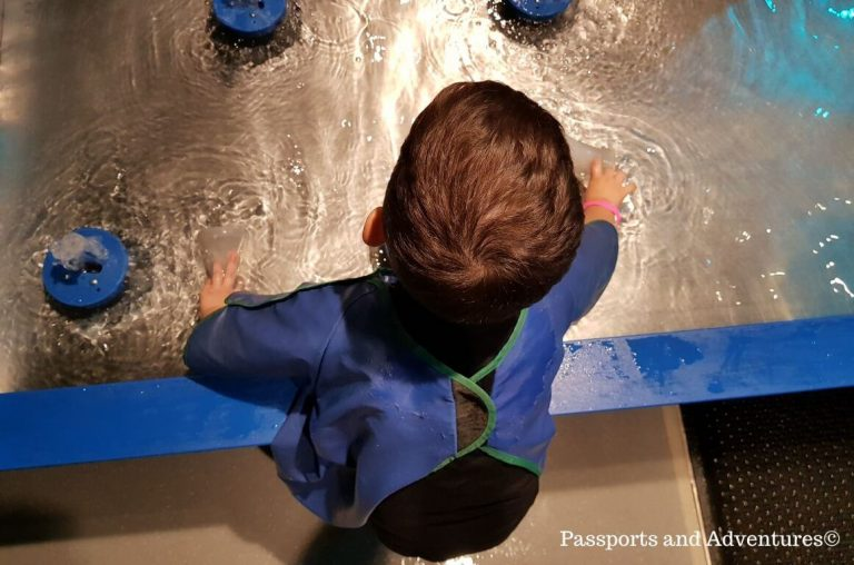 A young child in a blue apron playing at a water table in the Portland Science Museum
