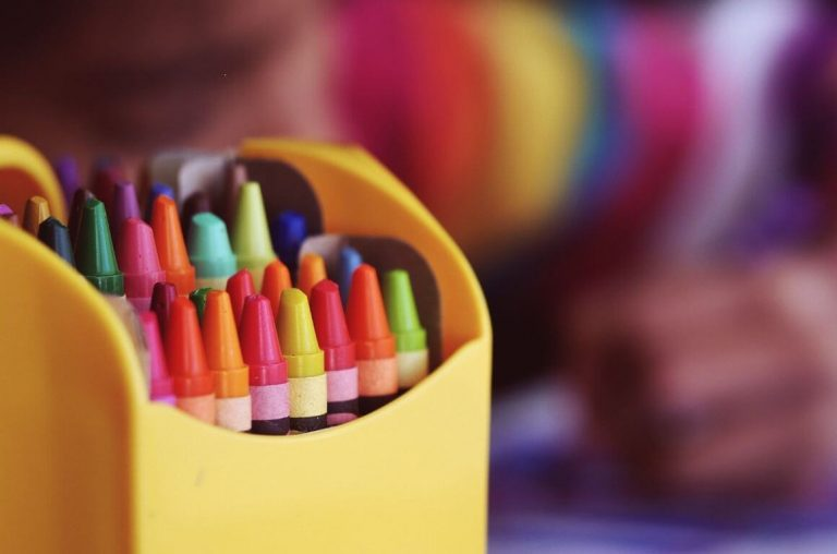 A picture of colourful crayons in a yellow container
