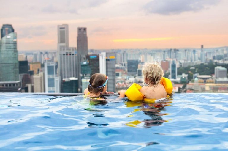 A picture of two kids in an infinity roof-top pool, one with yellow arm-bands on and one with goggles around their head