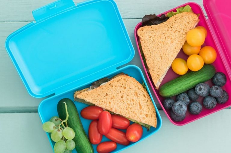 A picture of a blue lunch box and pink lunch box side by side with food in them