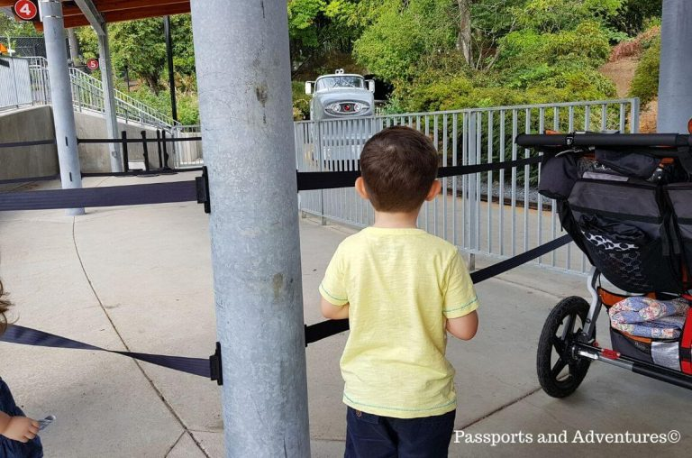A little boy waiting at a gate for the Oregon Zoo train