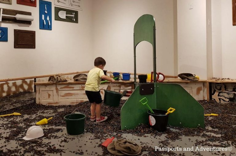 A little boy in a play construction area filling a bucket with 'muck'