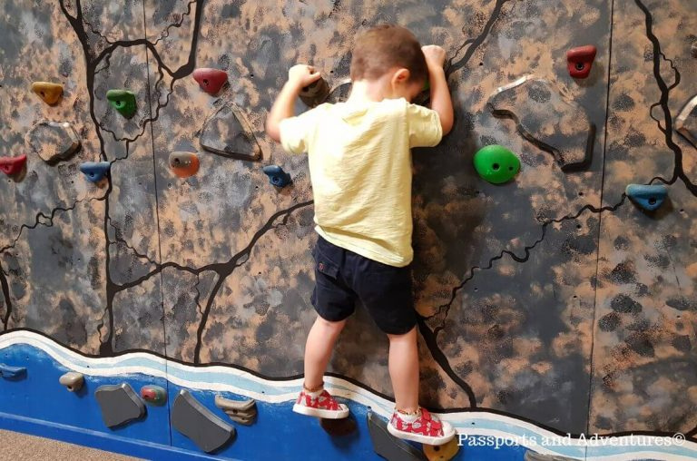 A little boy on a climbing wall at the Portland Children's Museum in Oregon