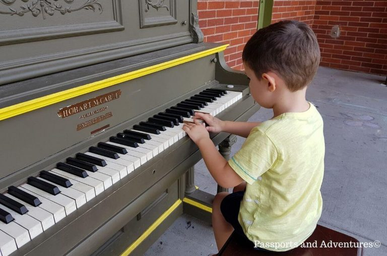 A little boy playing a piano outside the children's museum in Portland, Oregon
