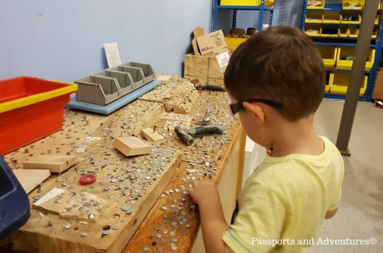 A little boy play hammering a nail into a board