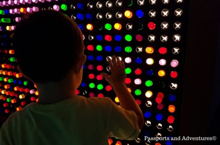A little boy in front of an illuminated board with a black background and light tubes of different colours