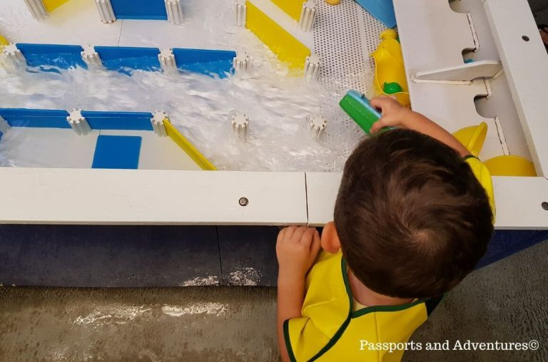 A little child at a water play area in a children's museum
