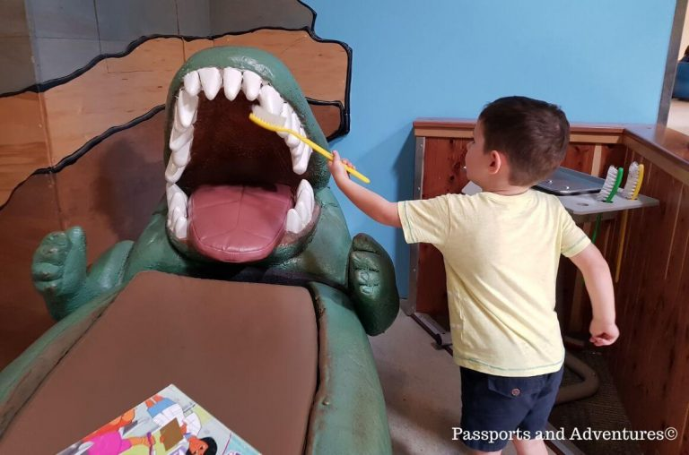 A little boy pretending to clean teeth on a play crocodile