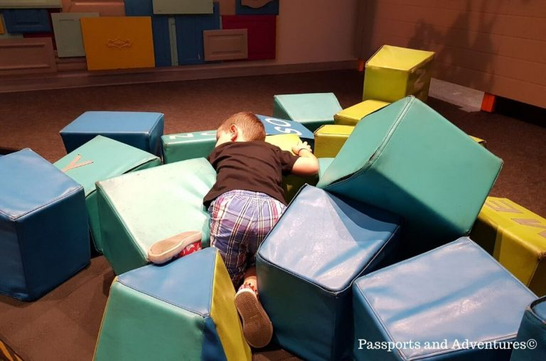 A little boy in a pile of soft play blocks in OMSI