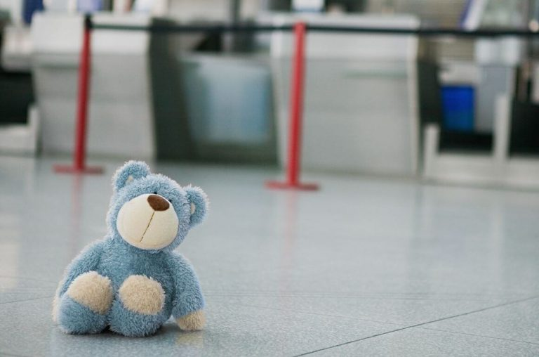 A blue teddy bear sitting on the floor at the check-in desks in an airport