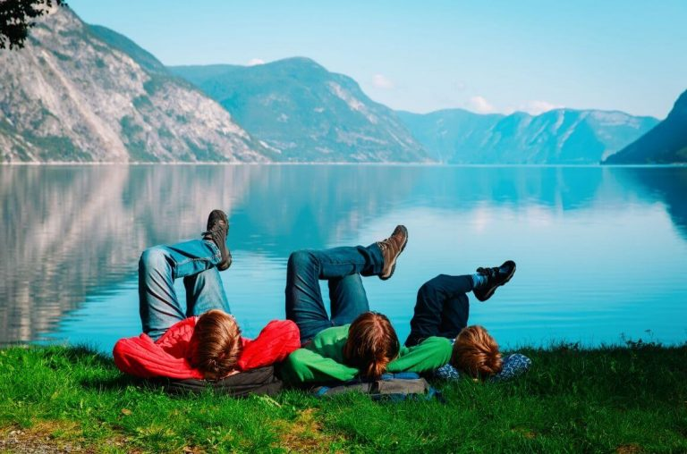 A picture of three kids lying on their back with their legs crossed in front of a blue lake with mountains in the background