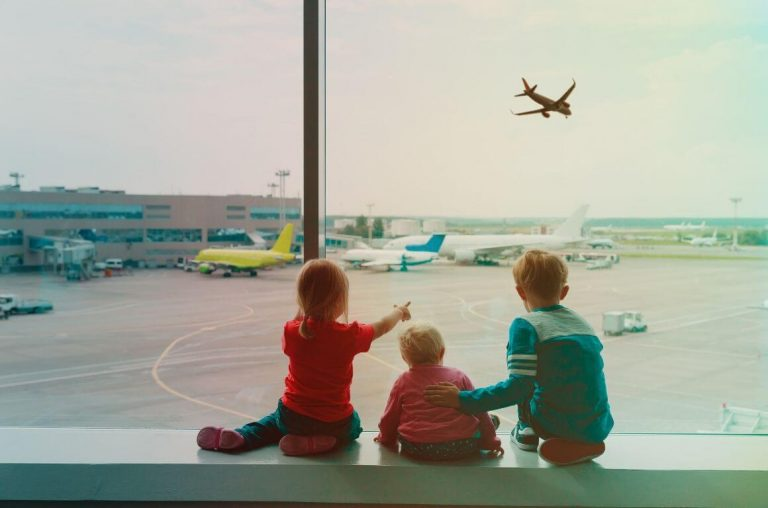 A picture of three young children sat in front of an airport window watching planes take off