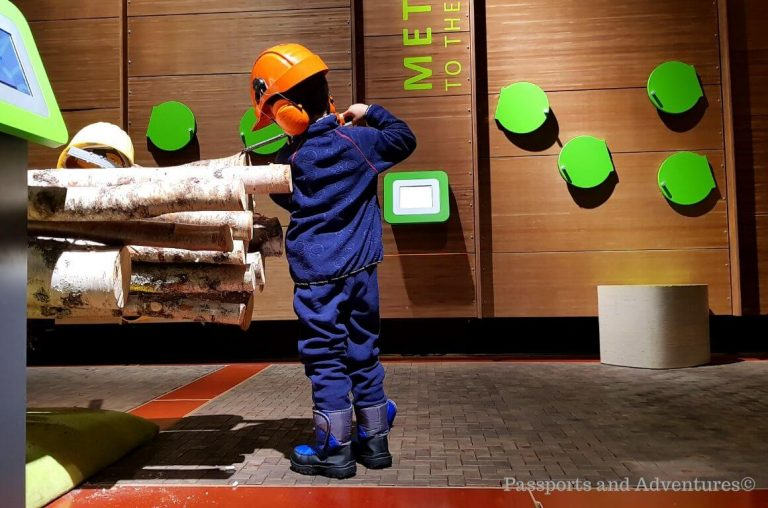 A little boy in navy blue base layers pretending to be a lumberjack in the Pilke Museum in Rovaniemi, Lapland