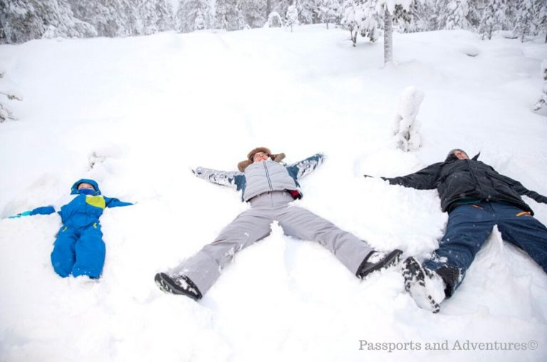 A family of three making snow angels in the snow in Lapland