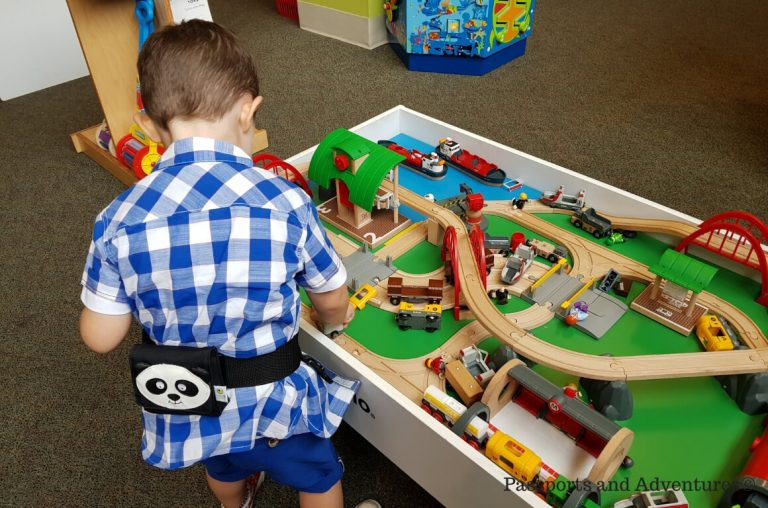 A little boy playing at a Brio train set table in Finnegans toys, Portland