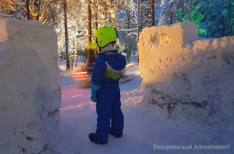 A little boy in a blue snowsuit and yellow helmet waiting to go on a snowmobile in Lapland