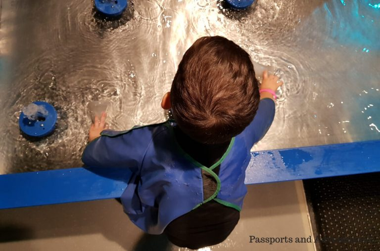 A little boy playing at the water table in the Oregon Museum of Science and Industry, one of the best things to do in Portland with kids