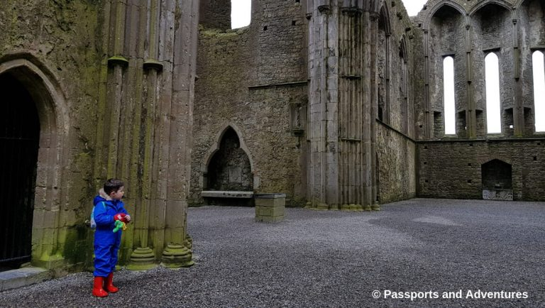 A little boy in a blue rain suit and red wellington boots standing in the grounds of the Rock of Cashel in Ireland