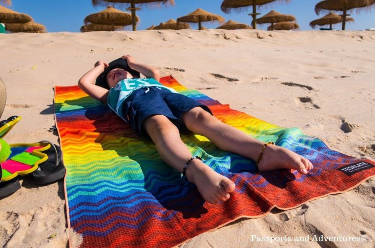 A little boy lying on a Tesalate Beach Towel on a beach