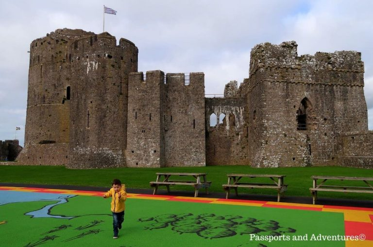 A boy in a yellow raincoat playing in the grounds of Pembroke Castle, Wales