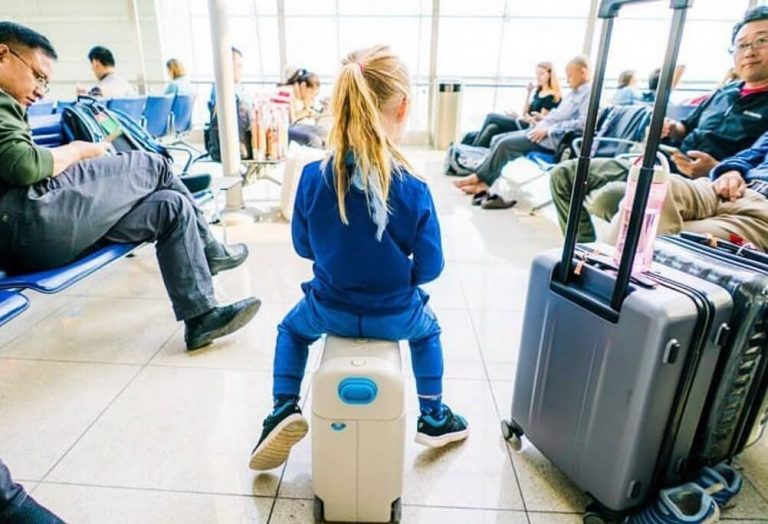 A picture of a girl on a Jet Kids bedbox in an airport departure lounge
