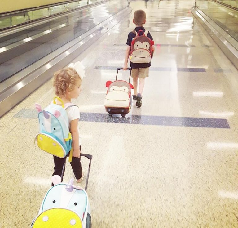 A picture of two kids pulling their hand luggage cases behind them in an airport